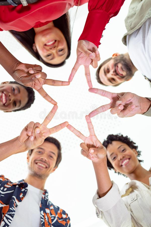 Business people forming star shape with their fingers in a modern office. Low angle view of diverse business people forming star shape with their fingers in a stock photography