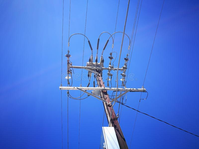 A Low angle view of Electricity High Voltage Transformer for Sending Power Line Energy Generation isolated on blue sky background. royalty free stock image