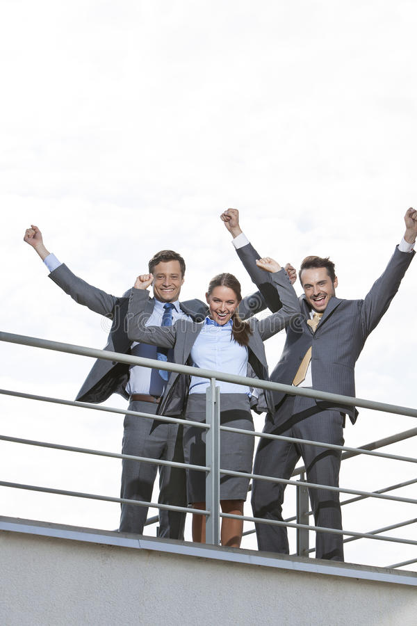 Low angle view of excited businesspeople with arms raised on terrace against sky stock images