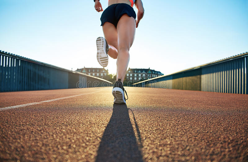 Low angle view of female jogger bounding forward. On a bright day towards apartment buildings stock image