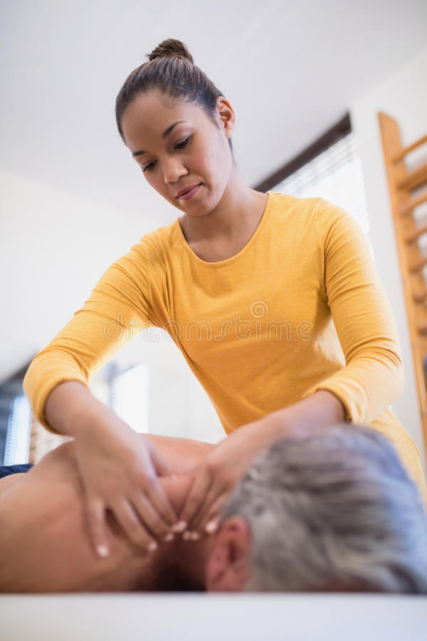 Low angle view of female therapist giving neck massage to male patient. At hospital ward royalty free stock image
