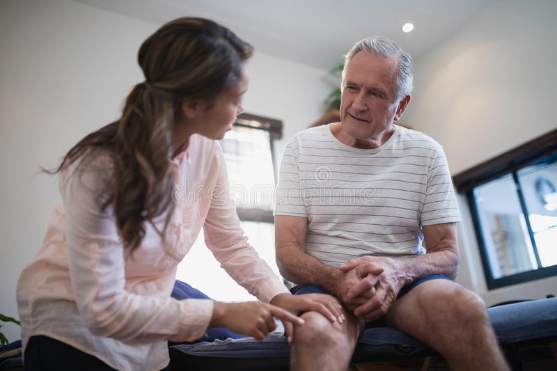 Low angle view of female therapist pointing at knee while male patient sitting on bed stock photos