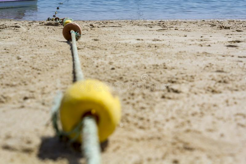 Low angle view of floating rope on the beach. Low angle view of marker buoys rope on the beach stock images