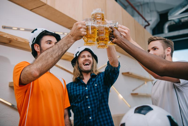low angle view of football fans in soccer ball hats celebrating victory and clinking beer glasses stock images