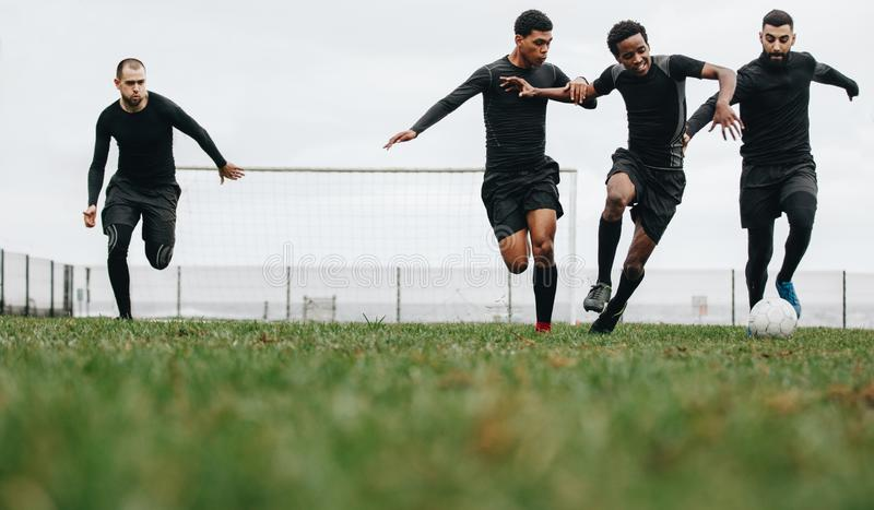 Low angle view of footballers playing on the field running for the ball. Group of men running for possession of ball while playing. Football stock image