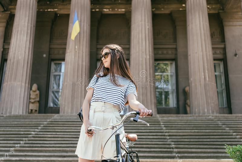 low angle view of girl in sunglasses looking away while standing with bicycle near beautiful building with columns stock image