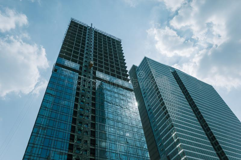 Low angle view of glass skyscrapers in Chengdu, China. Windows of Skyscraper Business Office in finance district in Chengdu, China. One building is under process royalty free stock photo