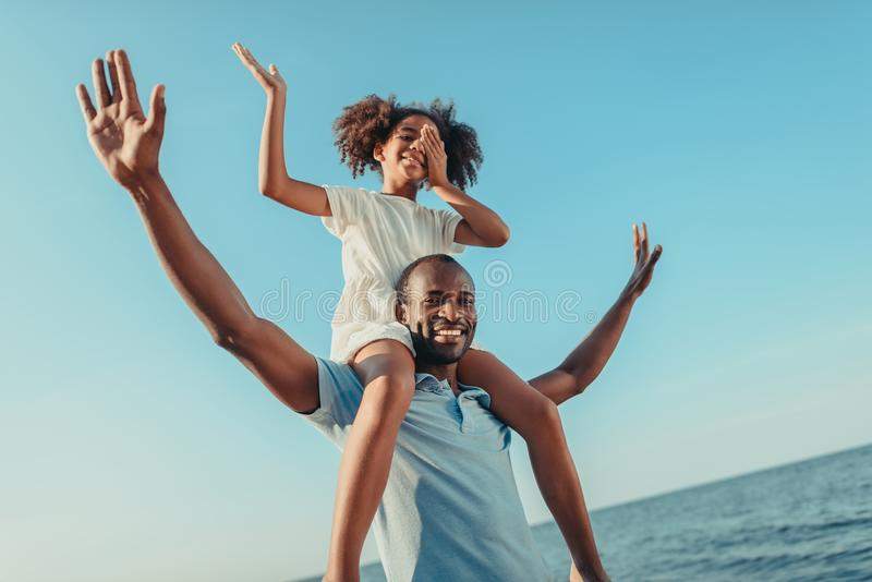 low angle view of happy african american father carrying daughter and having fun stock images