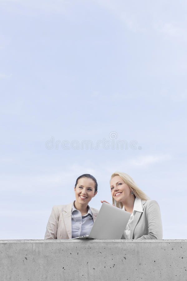 Download Low Angle View Of Happy Young Businesswomen With Laptop Looking Away While Standing On Terrace Against Sky Stock Image - Image: 33889153