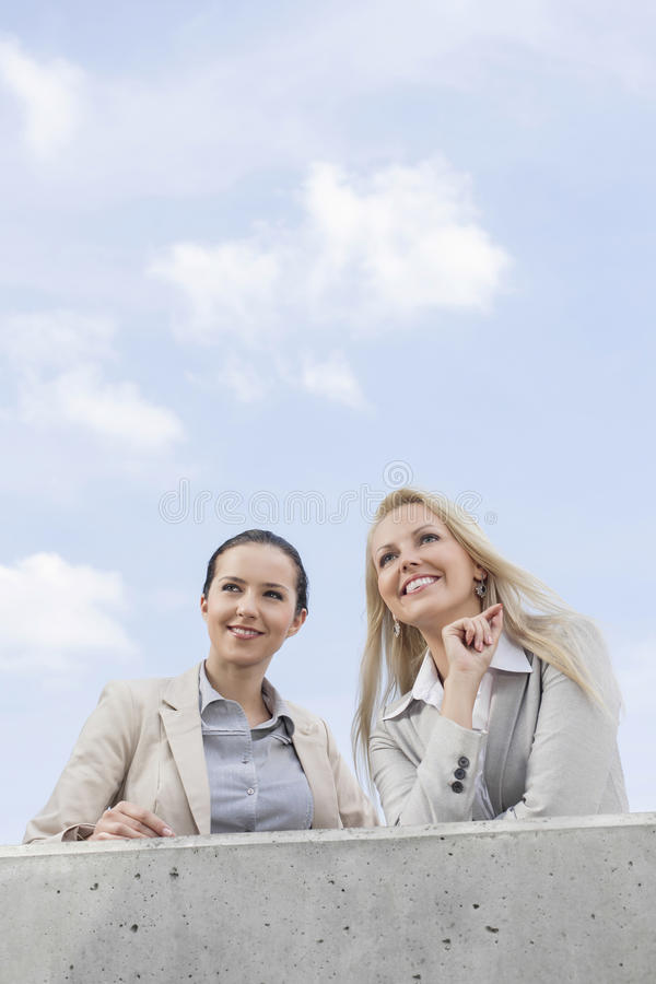 Download Low Angle View Of Happy Young Businesswomen Looking Away While Standing On Terrace Against Sky Stock Photo - Image: 33892940