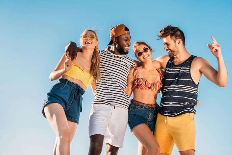 low angle view of happy young multiethnic friends smiling against royalty free stock photos