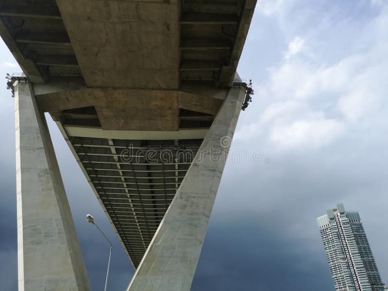 Low angle view of huge and stately bridge with cloudy sky and tower in the background, urban and futuristic concept. Bhumibol Bridge, Bangkok, Thailand stock image