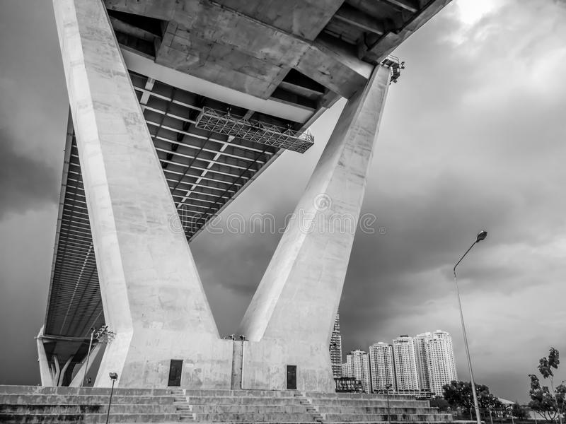 Low angle view of huge and stately bridge with cloudy sky and tower in the background, urban and futuristic concept. Bhumibol Bridge, Bangkok, Thailand royalty free stock images