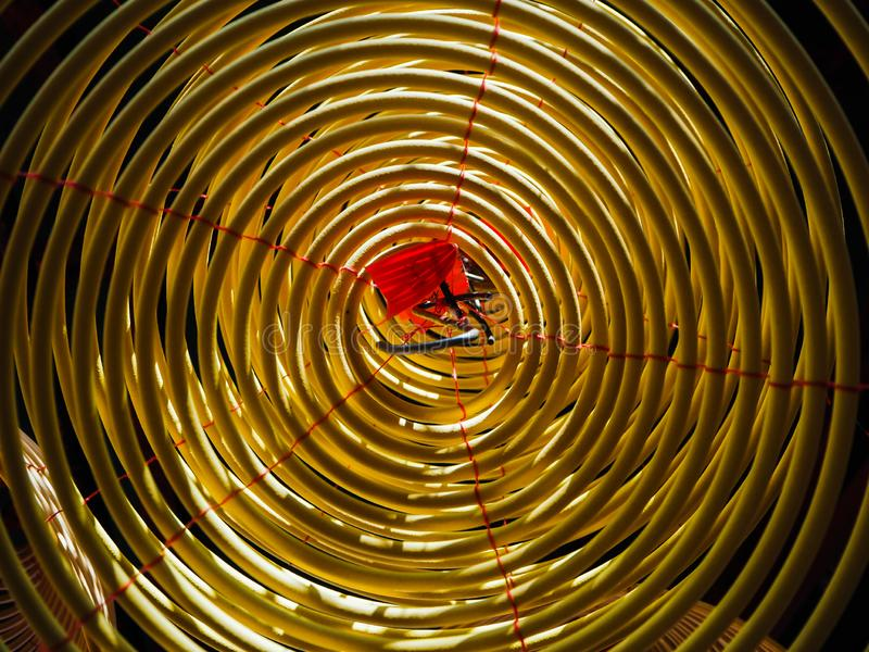 Low angle view on the inside of a large yellow incense coil hanging from the ceiling in a Chinese temple royalty free stock image