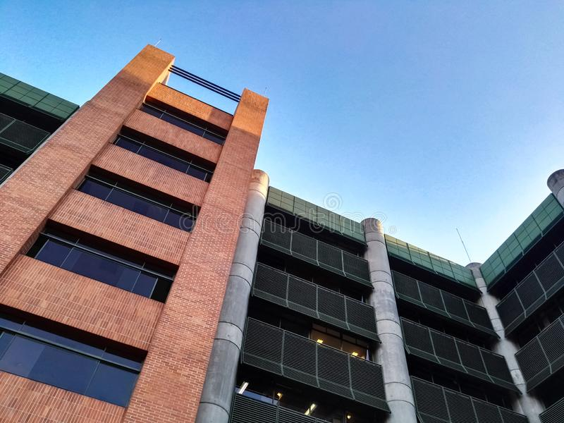 Low angle view of a large modern building with exterior brick and steel facade stock photos