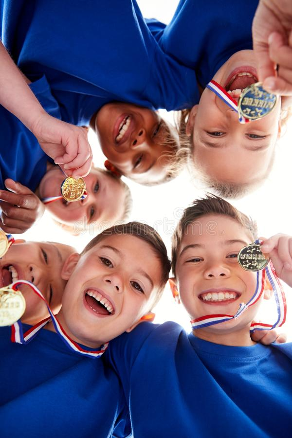 Low Angle View Looking Up Into Faces Of Children In Huddle On Sports Day stock images