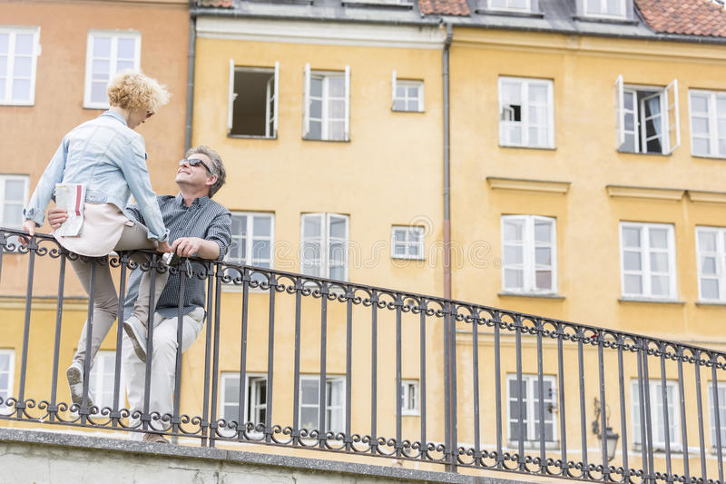 Low angle view of loving middle-aged couple by railing against building royalty free stock images
