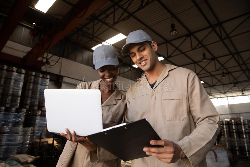 Male and female worker discussing on clipboard in warehouse. Low angle view of male and female worker discussing on clipboard in warehouse. This is a freight stock photos