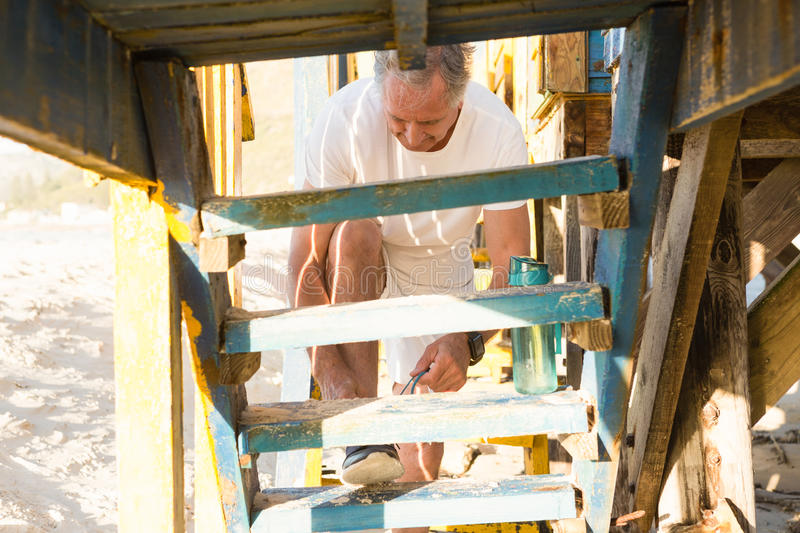 Low angle view of man tying shoelace while standing on steps. At beach hut royalty free stock photos