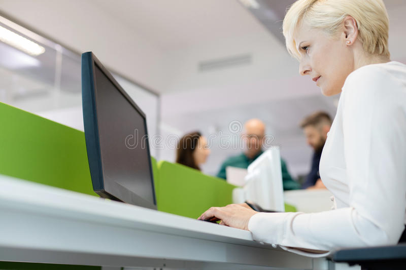 Low angle view of mature businesswoman using computer with colleagues in background at office royalty free stock photography