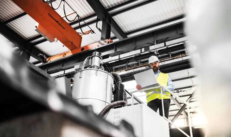 A low angle view of an industrial man engineer with laptop in a factory, working. A low angle view of a mature industrial man engineer with laptop in a factory royalty free stock image