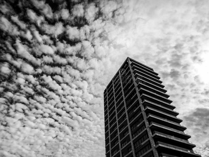 Low angle view of modern skyscraper on the background of а dramatic sky in Tel-Aviv, Israel. Perspective from below. royalty free stock photography