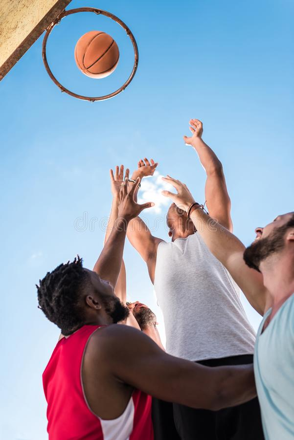 low angle view of multicultural basketball players struggling to royalty free stock photos
