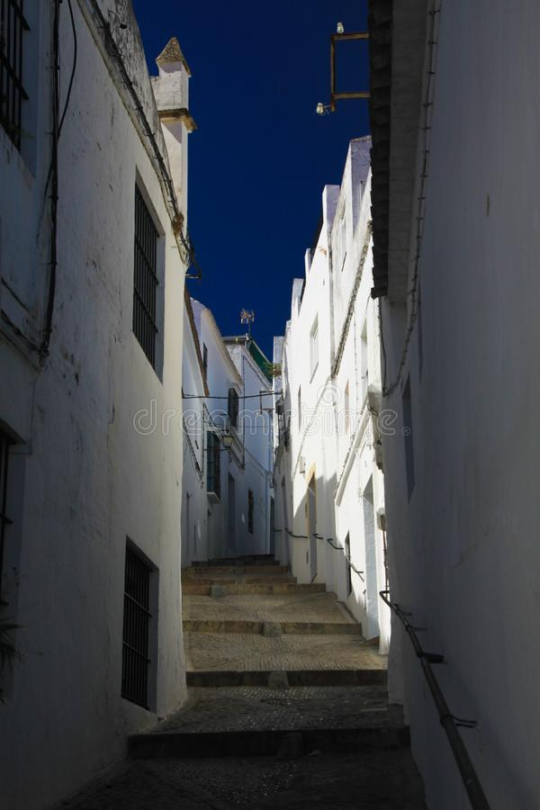 Low angle view on narrow empty alley with facades of white houses and steps upstairs contrasting with dark blue sky in traditional royalty free stock photo