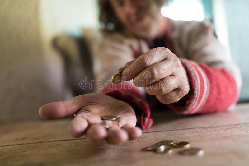 Low angle view of an old man in torn sweater counting Euro coins. On a rustic wooden desk in a conceptual image royalty free stock image