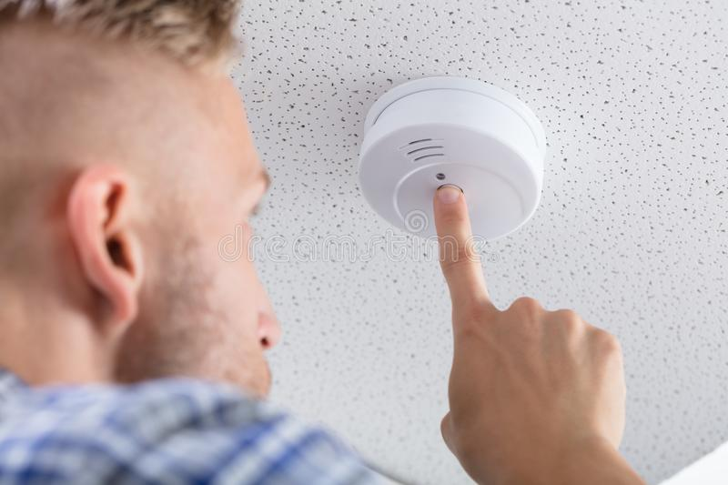 Person`s Hand Installing Smoke Detector On Ceiling. Low Angle View Of A Person`s Hand Installing Smoke Detector On Ceiling Wall At Home stock photos