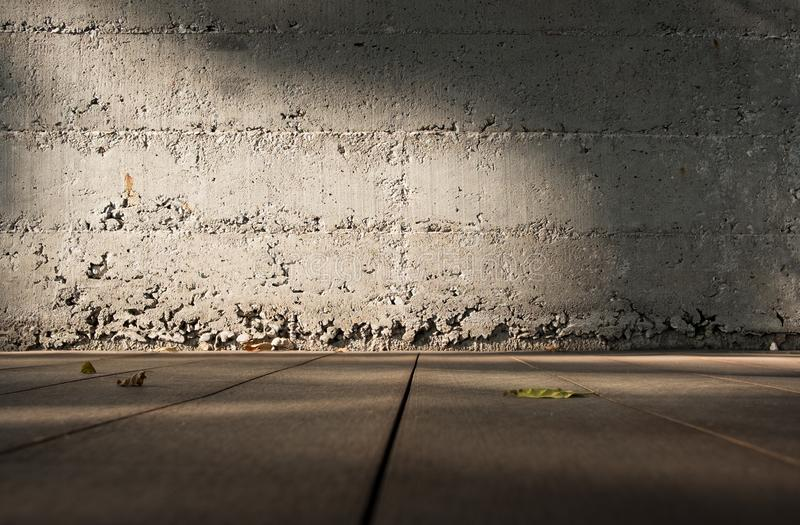 Low angle view perspective of wooden floor to blur grunge concrete wall with sunlight.Blank space for display of product. Of design stock images