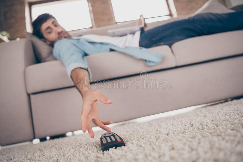 Low angle view photo of lazy mixed race arab guy lying comfy sofa can`t take tv remote control gadget need change royalty free stock photo