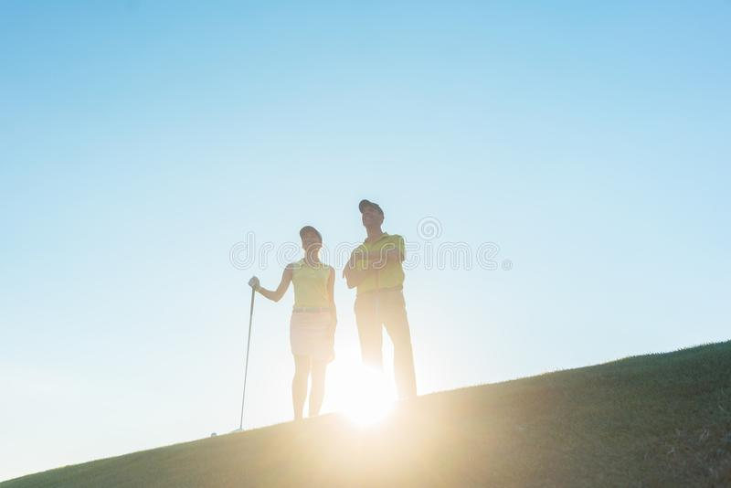 Silhouette of a man pointing while standing next to his partner royalty free stock photos