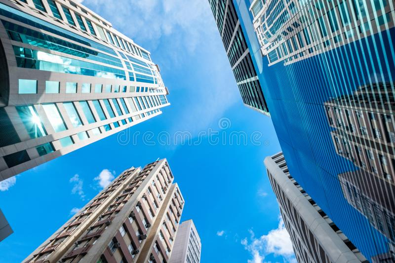 Low angle view of skyscraper buildings with glass windows and bl. Ue sky on sunny stock photo