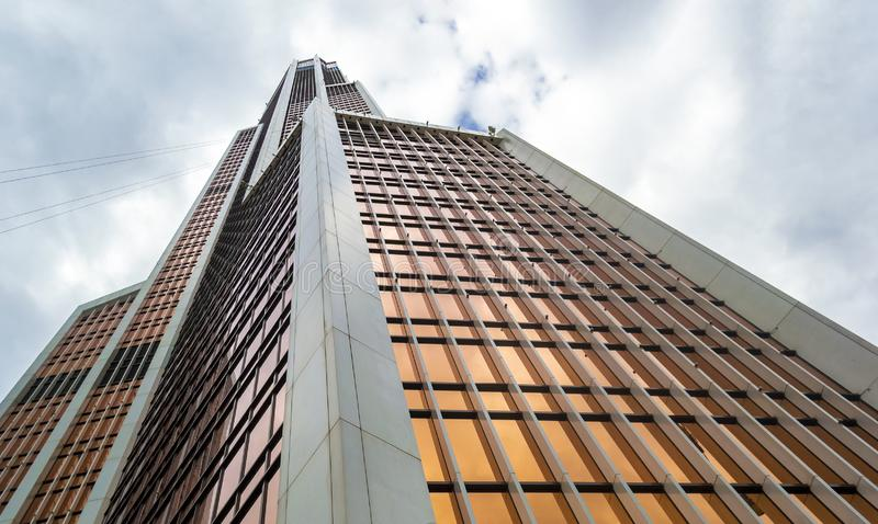 Low angle view of a skyscraper opposite sky. In dark weather stock images