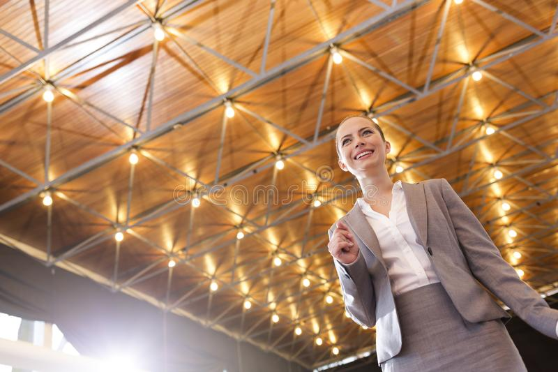 Low angle view of smiling young businesswoman in suit standing against illuminated roof stock image