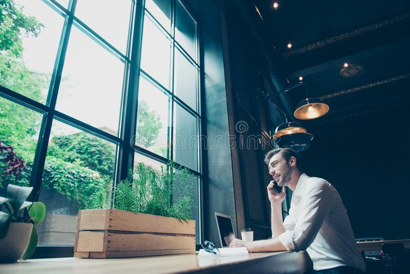 Low angle view of a successful young man, having a business conversation, at work station in a modern coworking, well dressed, s stock photography