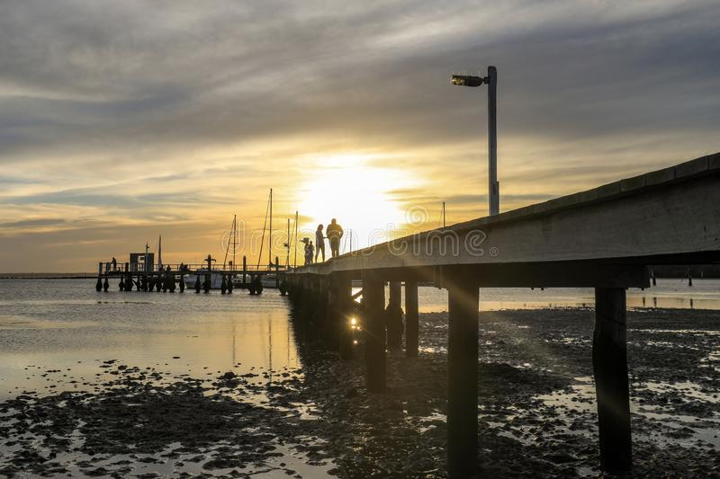 Low angle view of sun setting over ocean and pier. Low angle view of timber jetty leading to sun setting over ocean at low tide with silhouettes stock photography