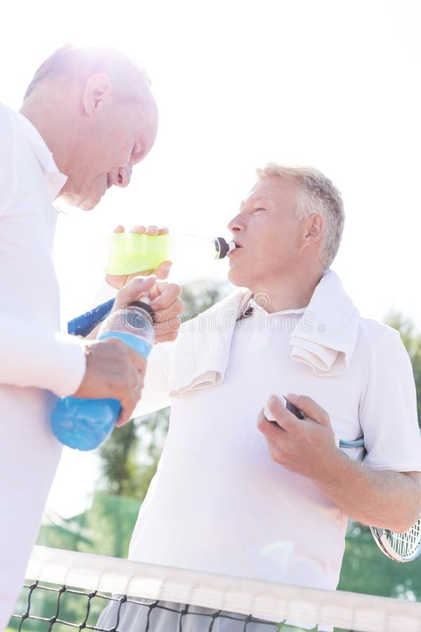 Low angle view of thirsty men drinking while standing by senior friend on tennis court against clear sky stock photography
