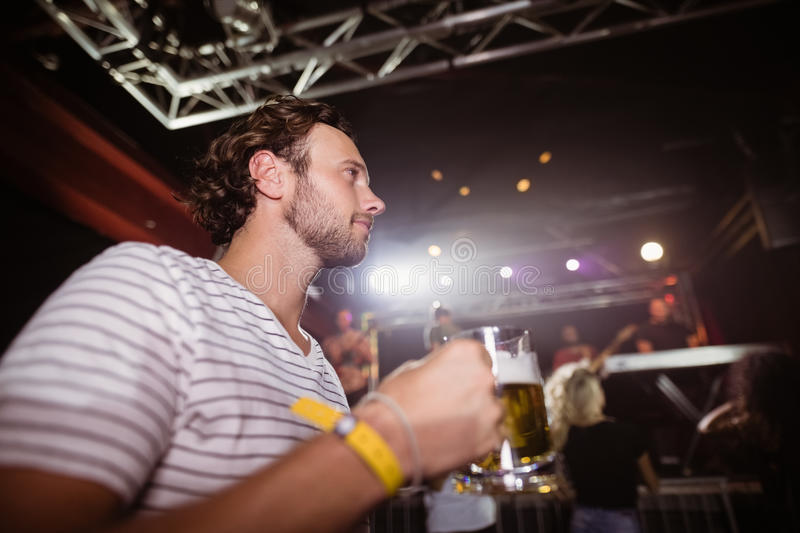 Low angle view of thoughtful man holding beer mug. At nightclub royalty free stock photos