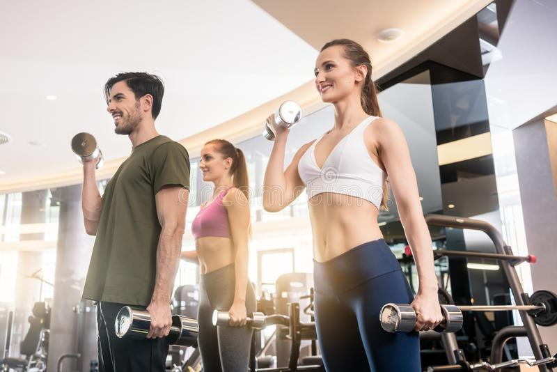 Three young people smiling while alternating dumbbell bicep curl. Low-angle view of three young people smiling while alternating dumbbell bicep curl exercise stock photography