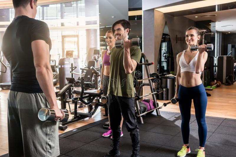 Three young people smiling while alternating dumbbell bicep curl. Low-angle view of three young people smiling while alternating dumbbell bicep curl exercise royalty free stock image