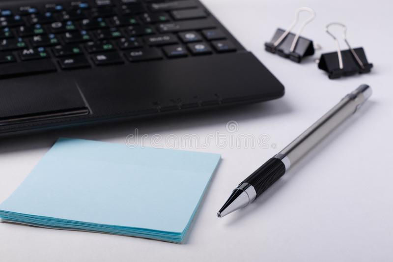 Workspace with laptop, pen and stickers on white background. Focusing on the foreground royalty free stock photography
