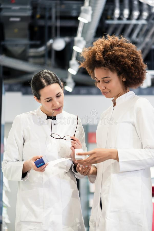 Reliable pharmacists analyzing a prescription and two different packages. Low-angle view of two reliable pharmacists analyzing together a medical prescription royalty free stock images