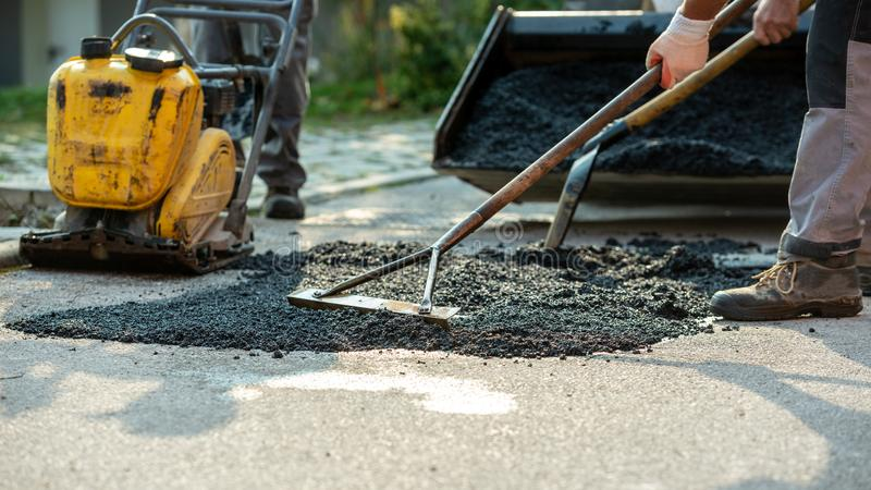 Low angle view of two workers arranging fresh asphalt mix with rakes and shovel royalty free stock photos