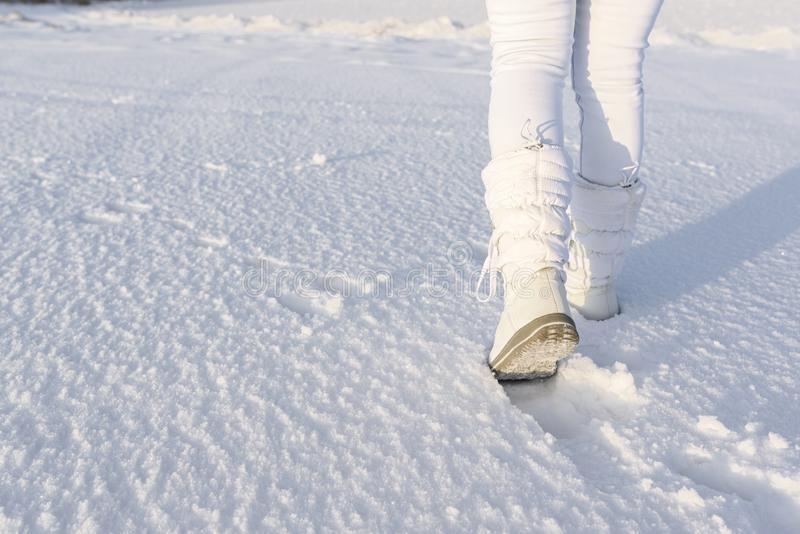 Low angle view of walking away female with white snow boots on. Low angle view of walking away female legs with white snow boots on, in deep snow. Winter royalty free stock images