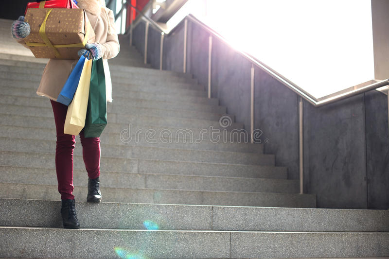 Low angle view of woman with gifts and shopping bags moving down steps royalty free stock photos