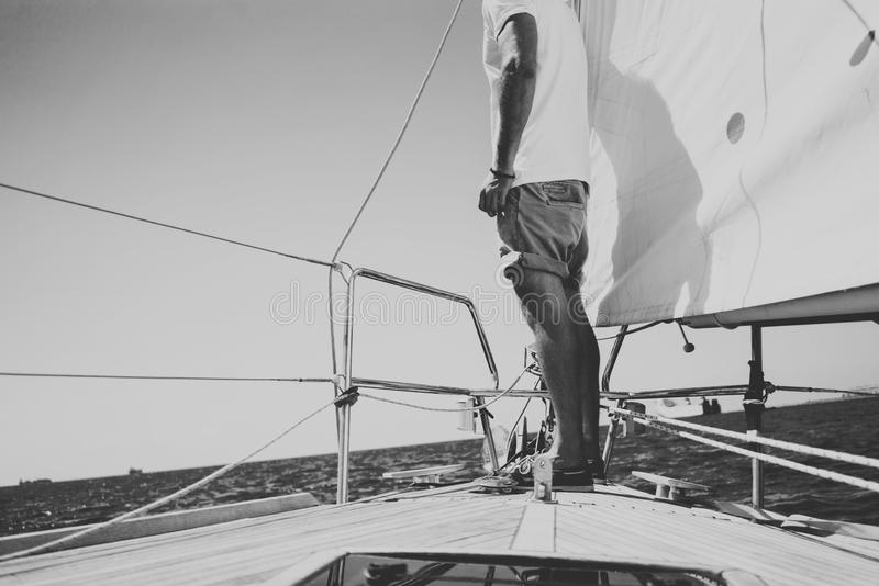 Low angle view of young bearded man standing on the yacht in sunny day. Horizontal black and white mockup stock images