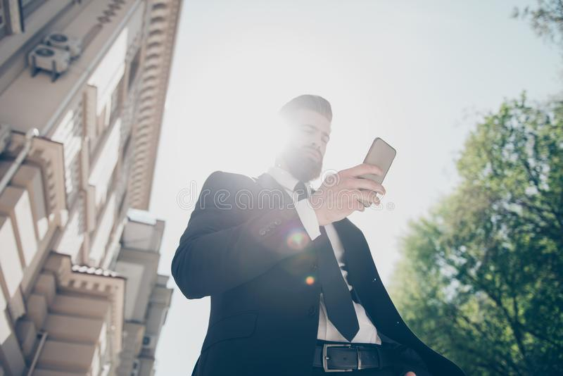 Low angle view of a young business man in a classy suit is checking his timetable by pda on the street at the sunny summer day. Ha stock images
