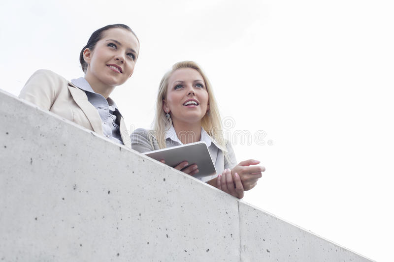 Download Low Angle View Of Young Businesswomen With Digital Tablet Looking Away While Standing On Terrace Against Sky Stock Image - Image: 33822121